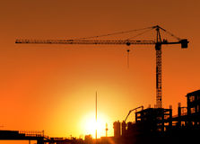 Construction Site and Crane. Horizontal photo of a construction site including a crane at sunset. The area is totally orange colored and all the buildings and Stock Image