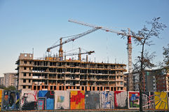 Construction site. With crane and graffitti on the fence stock image
