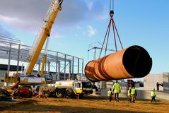 Steel pipe lift by a crane on a construction site royalty free stock images
