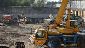 Construction site crane. People work crane excavator and trucks circa May 2013 in Vilnius, Lithuania. Industry construction site stock footage