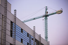 Construction site with crane whit purple sky at sunset. Royalty Free Stock Images
