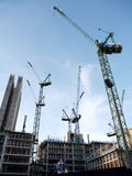 Construction site with cranes in the city. Construction and cranes on a building site Stock Photos