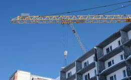 Construction site with cranes on sky background. The Builder works on the roof of a multi-storey building. royalty free stock images