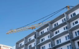 Construction site with cranes on sky background. The Builder works on the roof of a multi-storey building. Construction site with cranes on sky background. The Stock Photo