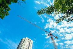 Construction site - cranes, treetops, the upper part of the house Stock Photography