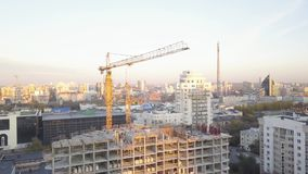 Construction site with cranes. Video. Construction workers are building. Aerial view. Top view of the construction site. In the city. Construction in the city stock video footage