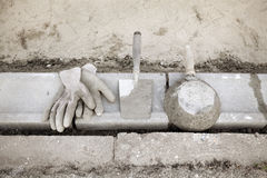 Construction site, curb stone and mason tools Stock Images