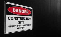 Construction Site Danger Sign Against Black Fence. Construction site warning sign, against a black painted fence royalty free stock photos