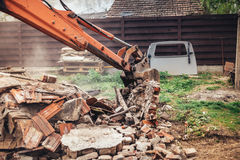 construction site details with excavator using scoop for demolishing and destroying old house Stock Image