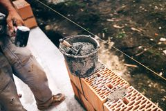 Construction site details, industrial plastic bucket with mortar, trowel and worker at building site Royalty Free Stock Image