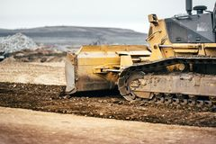 Highway construction site development with bulldozer moving earth, soil and leveling ground. Construction site development with bulldozer moving earth, soil and Royalty Free Stock Image
