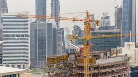 Construction site in Dubai timelapse, United Arab Emirates. Yellow cranes and workers in uniform. Business bay skyscrapers aerial top view stock video footage