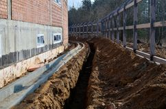 Construction site, dug trench in the ground, for pipe laying, water supply and communication. Installation of a fence royalty free stock images