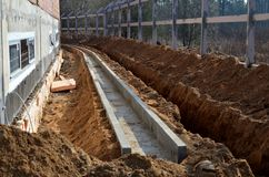 Construction site, dug trench in the ground, for pipe laying, water supply and communication. Installation of a fence royalty free stock image