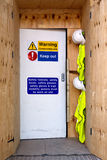 Construction site entrance safety notices. Photo of the entrance to a construction site with health and safety notices, hard hats and high visibility jackets Royalty Free Stock Image