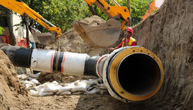 Construction Site. Excavator laying huge pipe in a trench Royalty Free Stock Photos