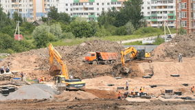 Construction site. Excavator loads clay into truck. MOSCOW, RUSSIA - JULY 07, 2017: Construction site. Yellow excavator loads clay using its big bucket into the stock video footage
