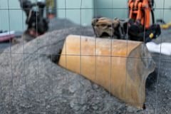 Construction site with excavator shovel. Fence in focus stock photos
