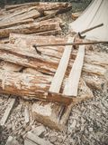 Construction site. Firewood with axes on a nature. Many logs wooden plank and three axes outdoor. Construction of a stock photos