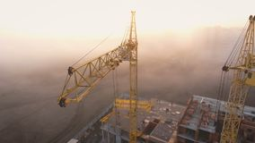 Construction site in the fog with a bird`s eye with tower cranes on the Sunset.