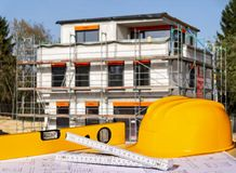 Construction site with helmet, spirit level, folding rule and blueprints Royalty Free Stock Photos
