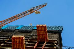 High-rise crane supplies material to a high-rise building Construction Site Of A high-rise Building. Construction Site Of A high-rise Building high-rise crane stock photo