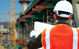 Construction site inspector. Inspector checking plan on construction site Royalty Free Stock Image