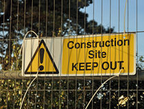 Construction site keep out sign on metal fence. With trees behind it royalty free stock images