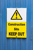 Construction site keep out sign. White and yellow construction site keep out sign on blue stock image