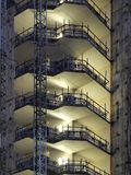 Construction site of a large high rise building at night with illuminated exposed stairs and floors with scaffolding and indus. The construction site of a large stock photo