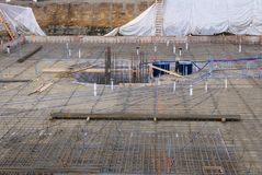 Construction pit building site with rebar foundation. Construction site laying the rebar foundation for a large building Royalty Free Stock Photo