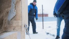 Construction site. A man hitting a wooden box with a hammer. A hook falls off from the box. Mid shot stock footage