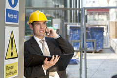 Construction Site Manager. A male manager on a construction site wearing a hard hat and talking on his phone Stock Photos