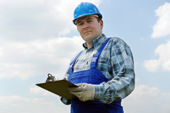 Construction site manager with notepad. Construction site manager wearing blue helmet and overall with notepad over sky background Royalty Free Stock Photos
