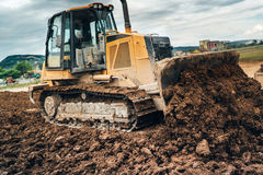 Construction site with mini bulldozer pushing earth and leveling ground Stock Image
