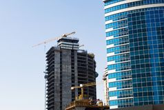 Construction site of modern skyscraper with cranes and finished skyscraper on the foreground stock photography