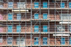 Construction site new apartment building with scaffolding and mason workers stock images