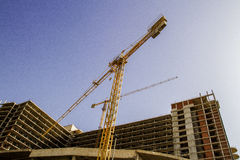Construction site. New building. Yellow tower crane against blue sky. Stock Photography