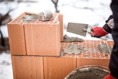 Construction site of new house during winter, man working with bricks and cement Stock Image