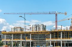 Construction site of new mall or shopping center in the city with cranes machinery, scaffolding, concrete with steel reinforcement. And workers Royalty Free Stock Photos