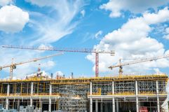 Construction site of new mall or shopping center in the city with cranes machinery, scaffolding, concrete with steel reinforcement. And workers Stock Photos