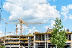 Construction site of new mall or shopping center in the city with cranes machinery, scaffolding, concrete with steel reinforcement. And workers Royalty Free Stock Image