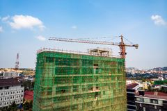 Construction site next to modern office, residential building. Working crane and safety net with cloud blue sky . Green grid. Prevent objects falling from royalty free stock image