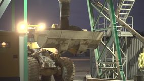Construction Site at Night. Heavy machine pouring sad or gravel into excavator shovel. Slow motion shot in the night. Bulldozer in use in the dark. Heavy stock footage
