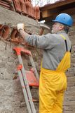 Construction site, old building demolishing. Construction worker demolishing old brick wall with chisel tool and hammer Stock Photography