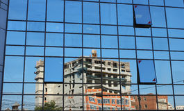 Construction site reflected in an office building. On a spring day Stock Photography