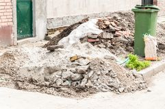 Construction site remains of building material on the ground by the foundation base dumped on the street for the garbage.  Royalty Free Stock Photography