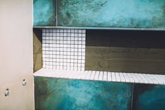 Construction site, renovation and improving bathroom area. Shower area with mosaic marble pattern installation close up. Details of construction site, renovation Royalty Free Stock Photo