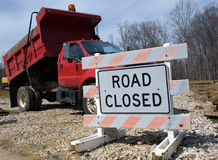 Construction Site Road Closed. Faded orange road closed sign and red dump truck blocking the entrance to a construction site Royalty Free Stock Image