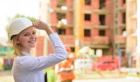 Construction site safety inspection. Construction project inspecting. Safety inspector concept. Woman inspector front. Construction site. Girl happy smiling royalty free stock photography